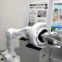 Handy: Honda Motor Co. unveils a prototype remote-controlled arm at its research center in Saitama Prefecture on Nov. 8. The arm will be used at the Fukushima No. 1 nuclear plant. | SATOKO KAWASAKI PHOTO