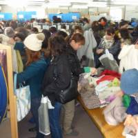 Community spirit: People from temporary housing units in Ishinomaki, Miyagi Prefecture, sort through free winter clothing and other items during a donation event organized by Marui Group Co., the Tokyo-based department store operator, on Dec. 11.