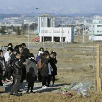 Life lesson: Students from Shuyukan Senior High School in Fukuoka visit a tsunami-hit area Saturday in Natori, Miyagi Prefecture. | KYODO