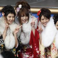 Fresh faces: Young women in kimono flash peace signs at a Coming of Age ceremony at Tokyo Disneyland in Urayasu, Chiba Prefecture, on Monday. | KYODO