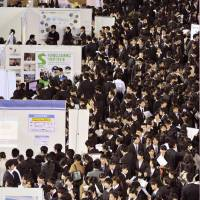 The drill: University students seeking jobs congregate at a recruiting event in December in Fukuoka where companies held seminars to explain their products and businesses. | KYODO