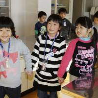 Orientation: A second-grade student (center) shows first-graders around Ota Elementary School in Minamisoma, Fukushima Prefecture, on Tuesday. | KYODO