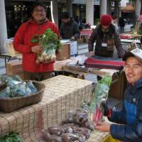 Youthful injection: Yusuke Shino (left), 28, who runs a farm in Chiba Prefecture with other young people, sells vegetables at a weekend farmers market held in Tokyo on Dec. 24. | KYODO