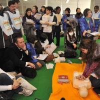 Crash course: Foreign residents of Tokyo take part in an emergency drill in Shibuya Ward on Friday. | YOSHIAKI MIURA