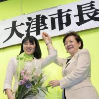 Double celebration: Naomi Koshi (left), newly elected mayor of the city of Otsu, and Shiga Gov. Yukiko Kada, hold hands Sunday evening to celebrate Koshi's victory. At 36, Koshi became the youngest-ever female mayor in Japan. | KYODO