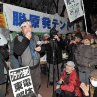 Standing firm: An antinuclear activist gives a speech Friday evening as he and other protesters refused to take down their tents at the Ministry of Economy, Trade and Industry by the 5 p.m. deadline. | YOSHIAKI MIURA