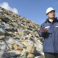 Raising awareness: Environment Minister Goshi Hosono stands in front of a mountain of tsunami debris at a temporary storage site in Ishinomaki, Miyagi Prefecture, on Saturday. | KYODO