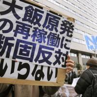 Not on board: A demonstration is held Wednesday outside the Ministry of Economy, Trade and Industry to protest the government's decision to endorse the results of stress tests on reactors at the Oi nuclear plant in Fukui Prefecture. | KYODO