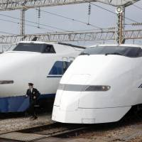 Last hurrah: A JR West official runs between a 100 series bullet train (left) and a 300 series at a car shed in Hakata, Fukuoka Prefecture, on Wednesday. The two series will be taken out of service on March 16. | KYODO