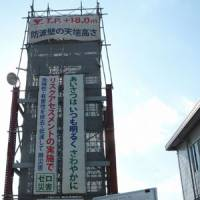 A Chubu Electric Power Co. official stands by a steel structure built to demonstrate the height of a planned sea wall against tsunami. | KYODO