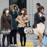 Bad hair day: Strong southerly winds hit Friday in the Marunouchi office district of central Tokyo. | KYODO