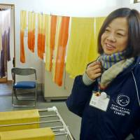 Ikumi Kitamura looks at hand-dyed products at a craft center in Koriyama, Fukushima Prefecture, on Feb. 1. | KYODO
