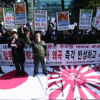 South Korean protesters, including one in a mask of Prime Minister Shinzo Abe, demand a full apology and redress from Japan over its wartime sexual enslavement of Korean women outside the Japanese Embassy in Seoul on Friday. The rally also slammed Tokyo's claim to the Seoul-controlled Takeshima Islands. | AP