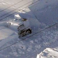Grim scene: The car in which a mother and her three children, aged 11 to 17, died from carbon monoxide poisoning Sunday lies buried in a snowdrift in the town of Nakashibetsu, eastern Hokkaido. | KYODO