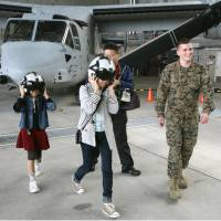 Buckle up: Residents of Ginowan get a chance to take a close look at tilt-rotor Osprey aircraft during a tour of U.S. Marine Corps Air Station Futenma in Okinawa Prefecture on Sunday. u.S. | U.S. FORCES JAPAN/KYODO