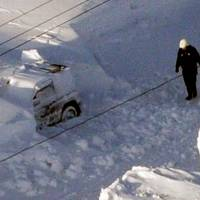 Seeking answers: An investigator walks Sunday afternoon near the car in which 40-year-old Kazuyo Miyashita and her three children died of carbon monoxide poisoning while the vehicle was trapped under snow the previous day in Nakashibetsu, Hokkaido. | KYODO