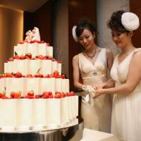 Dream come true: Koyuki Higashi (left) and Hiroko cut the cake at their wedding reception at Tokyo Disney Resort in Chiba Prefecture on Friday. | YOSHI YAMAGUCHI/AFP-JIJI