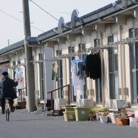 No progress: A man rides by temporary housing units in Ishinomaki, Miyagi Prefecture, on Feb. 27.  | SATOKO KAWASAKI
