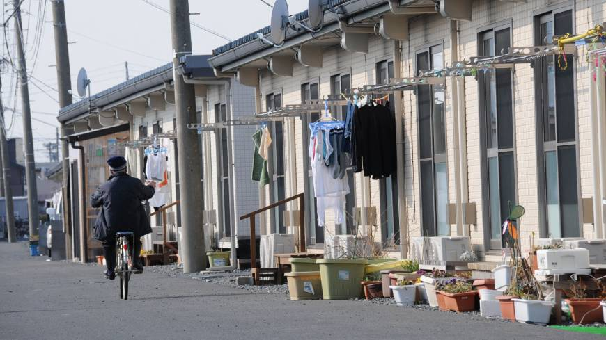 No progress: A man rides by temporary housing units in Ishinomaki, Miyagi Prefecture, on Feb. 27.