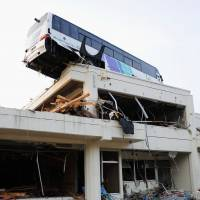Holding on: The district of Ogatsu in Ishinomaki, Miyagi Prefecture, is seen in September. Below: A bus remains stranded on the roof of Ogatsu's community center on March 23, 2011. | KYODO
