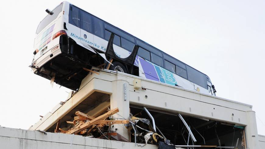 Holding on: The district of Ogatsu in Ishinomaki, Miyagi Prefecture, is seen in September. Below: A bus remains stranded on the roof of Ogatsu's community center on March 23, 2011.