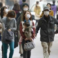 Haz-masks: Fukuoka residents venture outdoors wearing masks Saturday to protect themselves against a cloud of yellow sand that is drifting across from China. | KYODO
