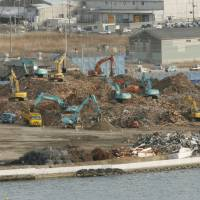 No place to go: Debris from the Great East Japan Earthquake and tsunami is processed at a temporary storage facility in Ishinomaki, Miyagi Prefecture, in February. | KYODO