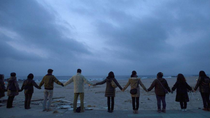 As one: People join hands Sunday morning on a beach in Iwaki, Fukushima Prefecture, ahead of the second anniversary of the Great East Japan Earthquake.