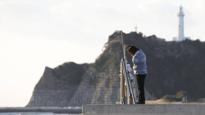 A woman on the coast of Tairausuiso in Iwaki, Fukushima Prefecture, prays Monday for family members killed in the earthquake and tsunami on March 11, 2011.