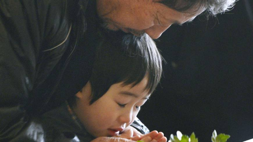 A man and child pray at a memorial ceremony in Kamaishi, Iwate Prefecture, the same day.