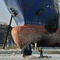 A man prays next to a ship in Kesennuma, Miyagi Prefecture. | KYODO