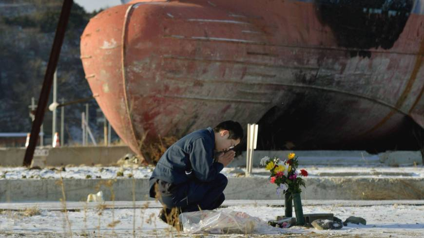 A man prays next to a ship in Kesennuma, Miyagi Prefecture.