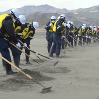 Engaged: Police search for the remains of tsunami victims on a riverside field near Okawa Elementary School in Ishinomaki, Miyagi Prefecture, on Monday. | AFP-JIJI