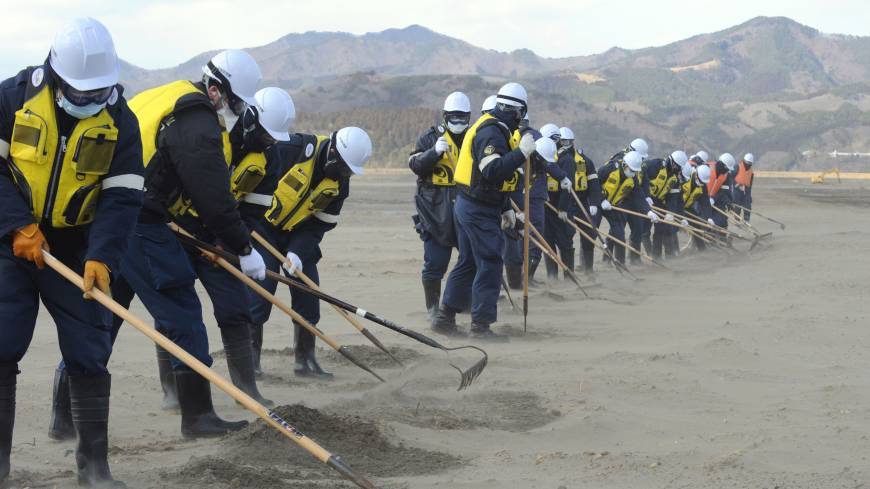 Engaged: Police search for the remains of tsunami victims on a riverside field near Okawa Elementary School in Ishinomaki, Miyagi Prefecture, on Monday.