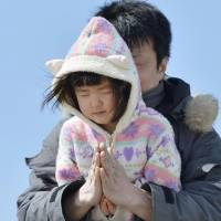 Companions: A man and his daughter pray together in Sendai's Wakabayashi Ward on Monday. | KYODO