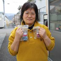 With them in spirit: A South Korean woman at a temporary housing unit in Ishinomaki, Miyagi Prefecture, holds handmade Jizo deities dedicated to the students at Okawa Elementary School who were killed by the 2011 tsunami. | JUN HONGO