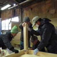 All for one: Three evacuees (right) attend a carpentry workshop in Minamisoma, Fukushima Prefecture, on Feb. 24. | MIZUHO AOKI