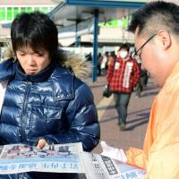 Read all about it: An Iwate Nippo official hands out an extra Monday in front of Matsuyama Station in Ehime Prefecture. | KYODO