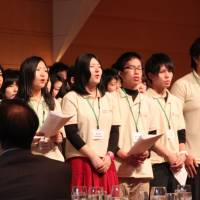 Survivors: Students from the Tohoku region sing as U.S. Ambassador to Japan John Roos (front right) and other guests watch at the conclusion of the 'BEYOND Tomorrow Global Leadership Academy 2013' forum at the Tokyo American Club on Sunday. | KYODO