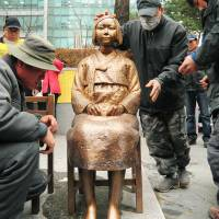 Not going away: A statue of a seated young Korean girl symbolizing the 'comfort women' is set up in front of the Japanese Embassy in Seoul in December 2011. | KYODO