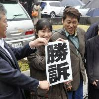 Vindication: Plaintiffs hold a 'victory' sign Wednesday after the Yamaguchi District Court ruled against Mazda Motor Corp.'s handling of temp staff. | KYODO