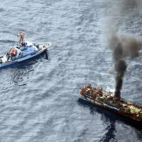 Tsunami flotsam: Smoke rises from a derelict Japanese ship after it was hit by cannon fire from a U.S. Coast Guard cutter last April in the Gulf of Alaska. | KYODO