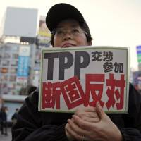 TPP foe: A protester holds a sign reading 'We oppose Japan's participation in the TPP talks' during a Thursday rally in Tokyo against the Trans-Pacific Partnership accord.   | AP