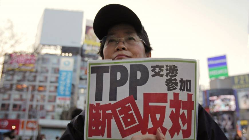 TPP foe: A protester holds a sign reading 'We oppose Japan's participation in the TPP talks' during a Thursday rally in Tokyo against the Trans-Pacific Partnership accord.