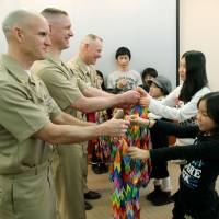 Thank you: Young evacuees from Fukushima Prefecture hand thousands of origami cranes to American military personnel at the U.S. naval base in Yokosuka, Kanagawa Prefecture, on Feb. 24 to show their appreciation for Operation Tomodachi. | KYODO