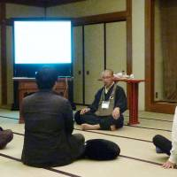 One with the universe: Job-hunting university students learn Zen meditation techniques from a Buddhist priest at a Tokyo hotel in December. | KYODO