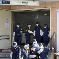 Rush-hour attack: Police investigate the scene of a stabbing rampage that left four people wounded near the Toyocho subway station in Koto Ward, Tokyo, Tuesday morning. | KYODO