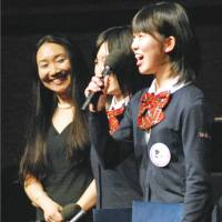 In your debt: Wakana Yuda (right), representing 70 high school students from disaster-hit Fukushima Prefecture, delivers a speech during a concert in New York on Friday to express their gratitude for international aid in rebuilding the region. | KYODO