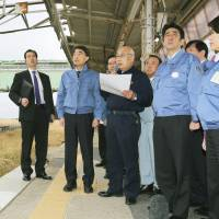Standing still: Prime Minister Shinzo Abe (right) listens as Tomioka Mayor Katsuya Endo describes the damage to Tomioka Station in Fukushima Prefecture on Sunday. | POOL