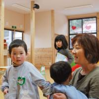 In demand: Emi Satomi cares for kids at the Kids Room Ohisama nursery in Kesennuma, Miyagi Prefecture, in February. | KYODO